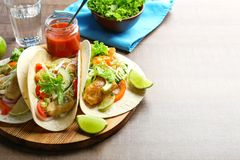 Wooden board with tasty fish tacos. On table Stock Image