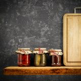 Wooden tray and jars on wooden shelf. Copy space for your decoration and products. Dark gray retro wall background.