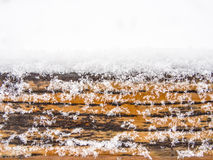 Wooden board, timber or plank covered with snow. Detail of weathered wooden bench covered in snow, top of timber, plank or board with copyspace on the top Royalty Free Stock Image