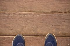 Wooden board top view photo with man feet. Worn male shoes on dusty wooden floor. Rough timber bridge. Or countryside walkway. Long distance travel banner Royalty Free Stock Photo