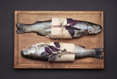 Wooden board with two fresh trout fish wrapped in paper. On black background Stock Images