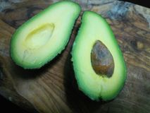 Two halves of avocado with a brown seed. On a wooden board royalty free stock image