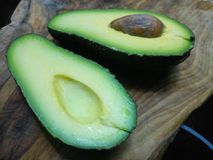 Two halves of an organic green avocado. On a wooden board stock photography