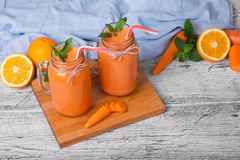 A wooden board with two mason jars with carrot smoothie, basil, oranges anf leaves of mint on a light background. Stock Images