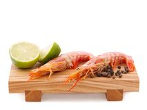 On a board, untreated royal shrimp are lime and a pile of black pepper.  on white. On a wooden board, two untreated large royal shrimp are a few lime pieces and Royalty Free Stock Images