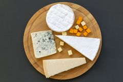 Wooden board with various types of cheese on dark background, top view. Flat lay. From above stock photography
