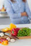 Wooden board with vegetables on a kitchen table Stock Image