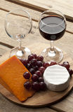 Wooden board with wine glass grapes and cheese Stock Images
