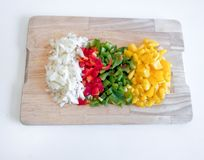 Wooden board with yellow, green, red and onion peppers, on white background stock photo