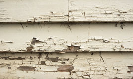 Wooden Boards Cracked Peeling Paint. The paint on the barge boards on a weatherboard house is cracked and peeling royalty free stock image