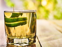 On wooden boards is glass with alcohol green lime drink . Stock Image