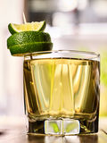 On wooden boards is glass with green drink and lime. Royalty Free Stock Images