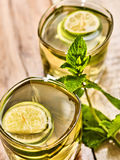 On wooden boards are glass with green drink and mint . Royalty Free Stock Photo