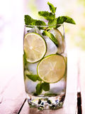 On wooden boards is glass with mohito and lime. Royalty Free Stock Image
