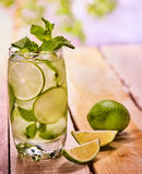 On wooden boards is glass with mohito and lime. Stock Photos