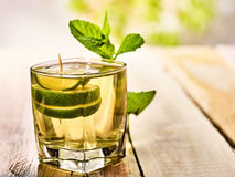 On wooden boards is glass with mohito and lime. Royalty Free Stock Photography