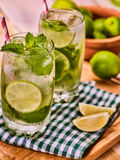 On wooden boards is glass with mohito and lime. Royalty Free Stock Photo