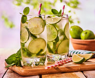 On wooden boards is glass with mohito and lime. Royalty Free Stock Photos