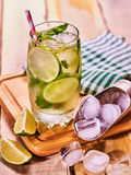 On wooden boards is glass with mohito and scoop ice. Stock Image