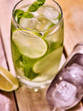 On wooden boards is glass with mohito and scoop ice. Stock Photography