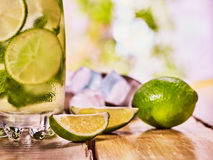 On wooden boards is glass with mohito and scoop ice. Royalty Free Stock Images