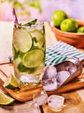 On wooden boards is glass with mohito and scoop ice. Royalty Free Stock Photography