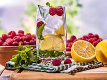 On wooden boards is glass with raspberry mohito and lemon. Royalty Free Stock Image