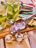 On wooden boards glasses with alcohol cocktail and shaker . Alcohol drink. On wooden boards two glasses with alcohol drink and ice cubes. A drink number forty royalty free stock image
