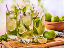 On wooden boards is glasses with mohito and lime. Royalty Free Stock Photos