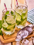 On wooden boards glasses with mohito and scoop ice. Stock Photos