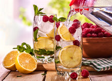 On wooden boards is glasses with raspberry mohito and jug. Royalty Free Stock Image