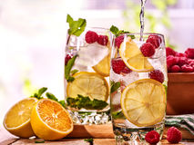 On wooden boards is glasses with raspberry mohito and jug. Stock Photo