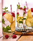 On wooden boards is glasses with raspberry mohito and lime. Stock Image