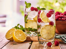 On wooden boards are glasses with raspberry mojito and lemon. Stock Photo