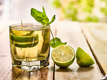 On wooden boards is mohito drink glass and half lime. Royalty Free Stock Photos