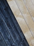 Wooden boards. In this picture we can see the diagonal wooden boards. The left half is dark and the right light Royalty Free Stock Photography