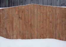 Wooden boards pine a fence are covered with wood stain white snow a snowdrift texture a background stock photography