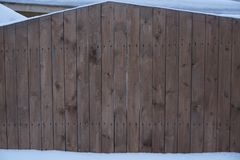 Wooden boards pine a fence are covered with wood stain white snow a snowdrift texture a background royalty free stock images