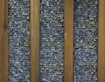 Wooden boards and small stones in a grid a background Royalty Free Stock Photography