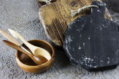 Wooden boards, spoons and bowl on grey concrete background. Props for food photography Royalty Free Stock Images