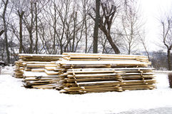Wooden boards stacked in piles on the ground and covered with snow Royalty Free Stock Photos