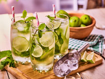 On wooden boards three glasses with mohito and lime. Stock Photos