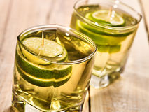 On wooden boards two glasses with green drink and lime. Stock Photography