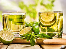 On wooden boards two mohito drink glass and half lime. Royalty Free Stock Images