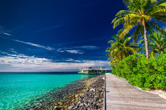 A wooden boardwalk along the beach under palm trees. And a restaurant Stock Photos