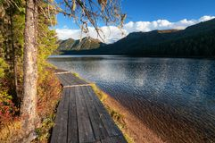 Wooden boardwalk along the lake in the mountains. Wooden boardwalk along Rakhmanovskoe lake in East Kazakhstan, Altai mountains Stock Photos