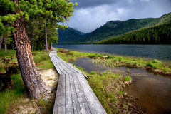 Wooden boardwalk along the lake in the mountains Royalty Free Stock Image