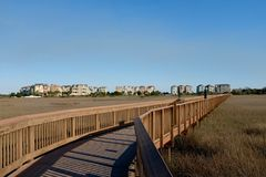 Wooden Boardwalk and Coastal Community Stock Photo