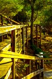 Wooden boardwalk leading to the sandy beach, the path by the sea Stock Images