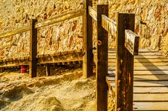Wooden boardwalk leading to the sandy beach, the path by the sea Royalty Free Stock Photo